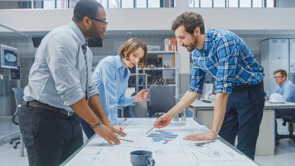 Drei Mitarbeiter diskutieren über die Weiterentwicklung eines physischen Produktes