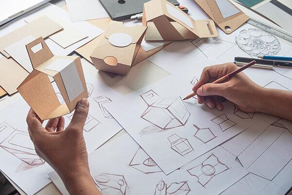 Grafiker zeichnet physische Verpackung und baut diese nach
